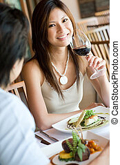 Having Dinner - A young woman smiling whilst eating dinner...