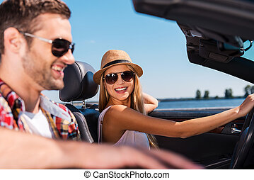 Having freedom to go anywhere. Beautiful young couple enjoying road trip in their convertible while beautiful woman looking at her boyfriend and smiling