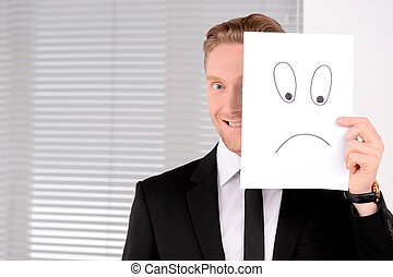 Having fun at work. Cheerful young businessman holding a poster in front of his face