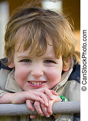 Having Fun - Close up of a young boy outside smiling and...