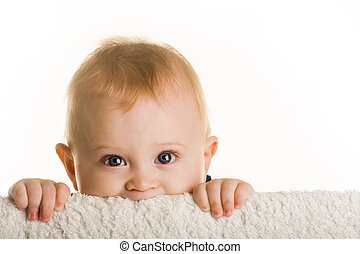Having fun - Face of curious baby peeping out of board over...