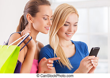 Having fun on shopping. Two beautiful young women in dresses holding shopping bags and looking at the mobile phone
