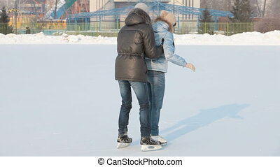 Having fun on skating rink - Happy couple spending time on a...