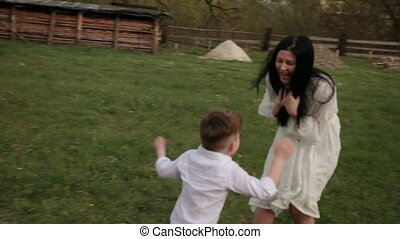 Having fun running, toddler boy playing in park with mom, mother plays her son