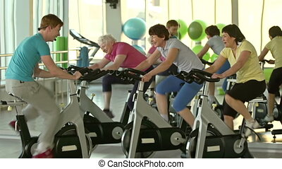 Having Fun - Side view of cycling workout of three women and...