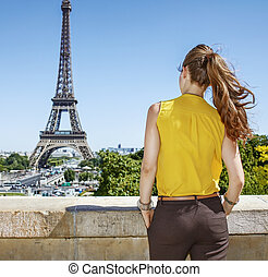 Seen from behind young woman in bright blouse in Paris,...