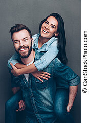 Having fun together. Handsome young man piggybacking beautiful woman and smiling while standing against grey background