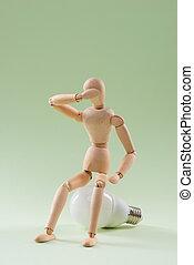 Having no idea. Wood figure mannequin sitting on an incandescent light bulb