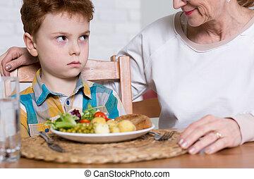 Having poor vegetables appetite - Irritated boy, sitting at ...
