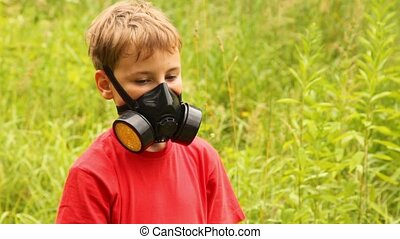 having put on a gasmask the boy is standing