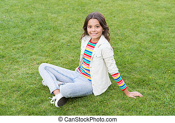 having rest in summer park. concept of rest and relaxation. spring nature enjoyment. cute girl rest on fresh spring grass. kid relaxing on the grass. Beautiful girl relaxing on grass. vacation time