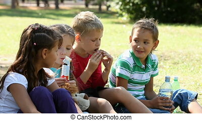 Having snack - Five children sitting on grass in the park...