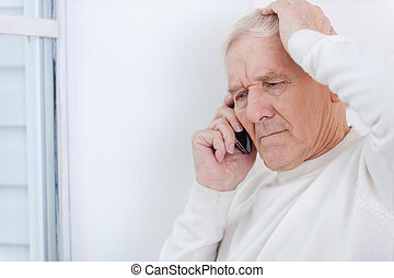 Having some troubles. Frustrated senior man talking on the mobile phone and touching his head while leaning at the wall