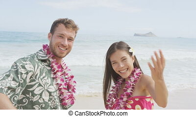 Hawaii beach couple saying welcome and come here showing hand gesture waving hand gesturing. Portrait of Asian woman and Caucasian man on beach Aloha Hawaiian shirt with flower leis and typical attire