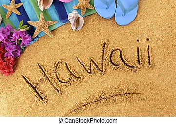 The word Hawaii written on a sandy beach, with flowers, beach towel, starfish and flip flops.