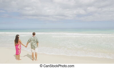 Hawaii honeymoon couple holding hands on tropical beach walking in Hawaiian apparel, pink sarong dress and green Aloha shirt for Polynesian cultural tradition. Young people holding hands happy in love