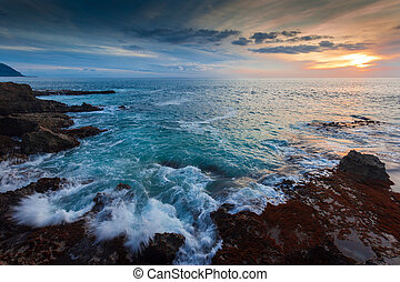 Waves are splashing up on the shores at Kaena Point in Hawaii. Shot at dusk.