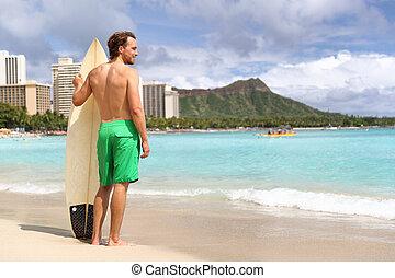 Hawaii surf man surfer surfing on Waikiki beach. Athlete standing with surfboard looking at ocean water, diamond head mountain in the landscape background, hawaiian tourist landmark. Honolulu, Oahu