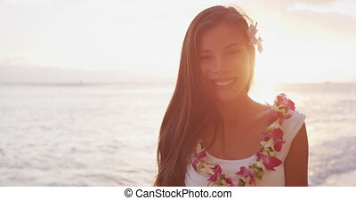 Woman portrait video looking at camera smiling. Hawaii woman wearing lei flower necklace on beach sunset for luau party or honeymoon wedding in Waikiki beach, Honolulu, holiday travel. SLOW MOTION