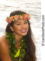 hawaiian girl with flowers on lava cliffs by the ocean