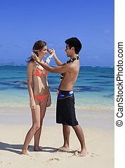 hawaiian man puts a lei on a young woman