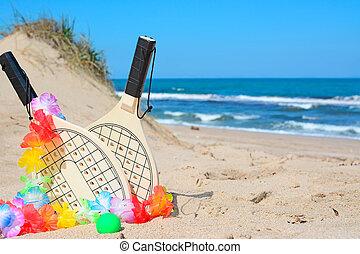 hawaiian necklace and beach rackets