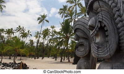 Hawaiian Tikis in the foreground with a sandy palm tree...