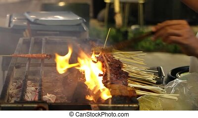 Street Hawker Vendor Grilling Meat Satay over Charcoal Barbecue Pit with Open Flames in Southeast Asia 1920x1080