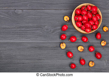 Hawthorn berry in bowl on a black wooden background with copy space for your text. Top view