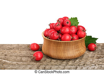 Hawthorn berry with leaf in a bowl on wooden table with white background