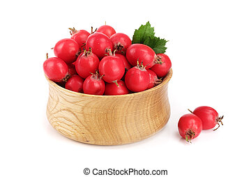 Hawthorn berry with leaf in a wooden bowl isolated on white background close-up