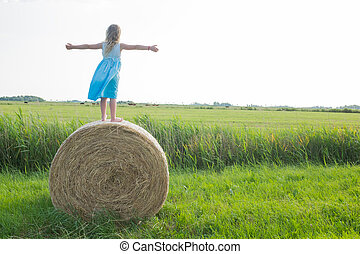 Happy young girl standing on a hay bale