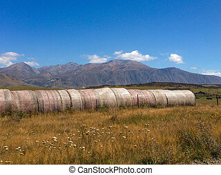 hay bales in front of mountains on the South Island of New Zealand