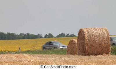 Hay Bales in the background  road with riding cars