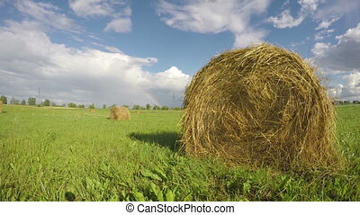 hay bales on field and rainbow