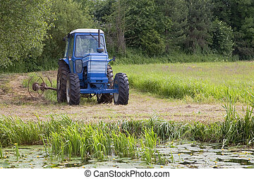 hay making time - a blue tractor fitted with hay turning ...