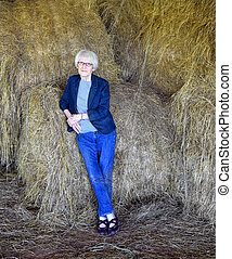 Elderly woman leans against the rolls of hay put up in her barn.  She is wearing jeans and a denim jacket.  Her expression is thoughtful.