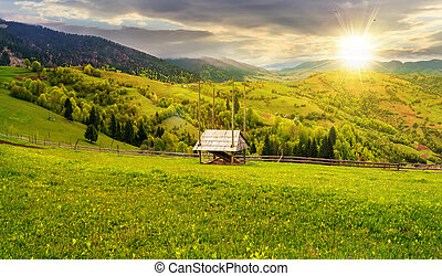 hay shed on a grassy field in mountains at sunset