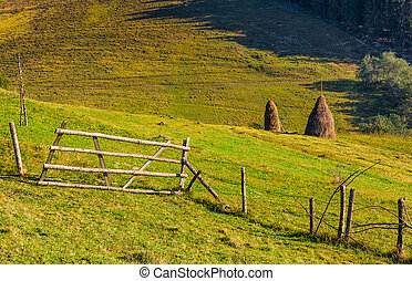 hay stacks behind the fence on rural field. lovely...