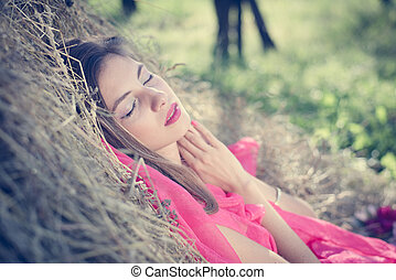 hay time: portrait of beautiful blond young woman having fun sleeping or praying on green summer outdoors copy space background