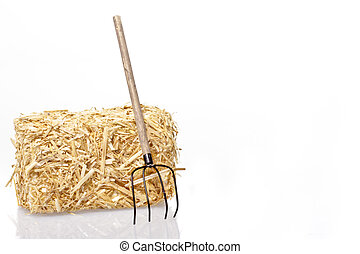 Haybale with tool on a white background