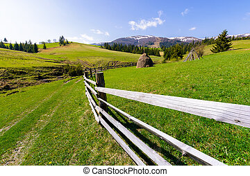 haystack behind the wooden fence on a grassy hill. beautiful...