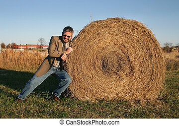 Haystack - Man in jacket, tie and jeans pushing on a...