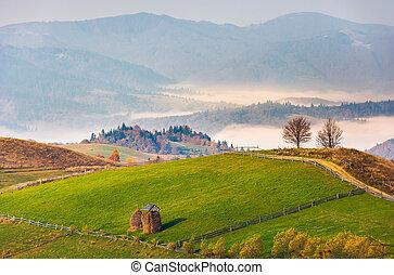 haystack on rural fields in foggy mountainous area....