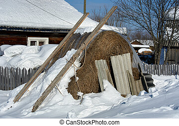 Haystack under the snow in the village