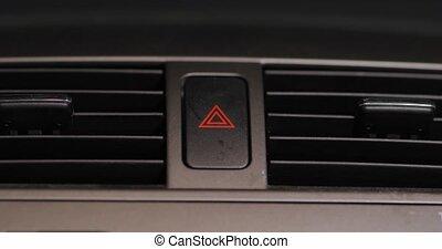 Pressing the hazard lights emergency signal button on a car