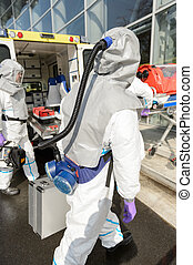 Hazardous material medical team with equipment walking...