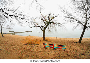Haze morning on beach photo with colored bench on sand