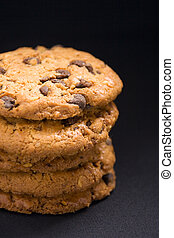 A stack of hazelnut and chocolate chips cookies on a dark background