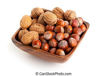 hazelnut and walnut in the wooden bowl. isolated on the white background